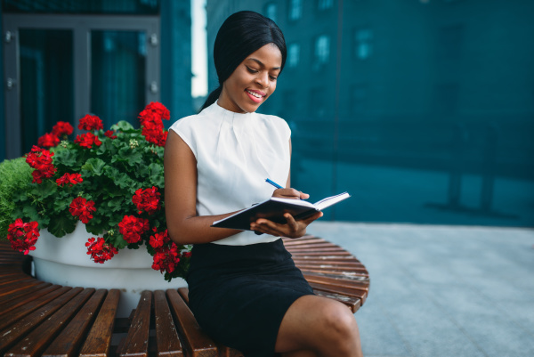 businesswoman writes in notepad in front