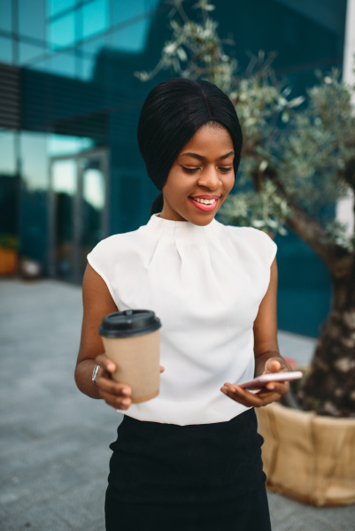 black business woman with coffee uses
