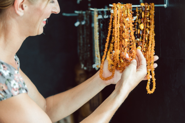 woman looking at a necklace made
