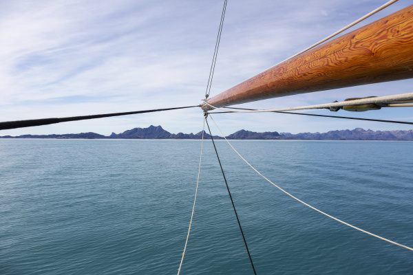 wooden sailboat mast over sunny blue