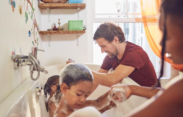 parents giving toddler daughters bubble bath