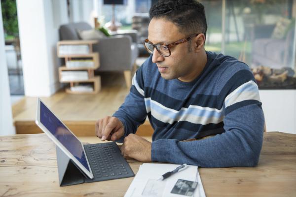 focused man paying bills at digital