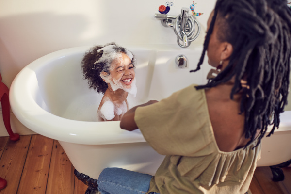 mother giving playful daughter bubble bath