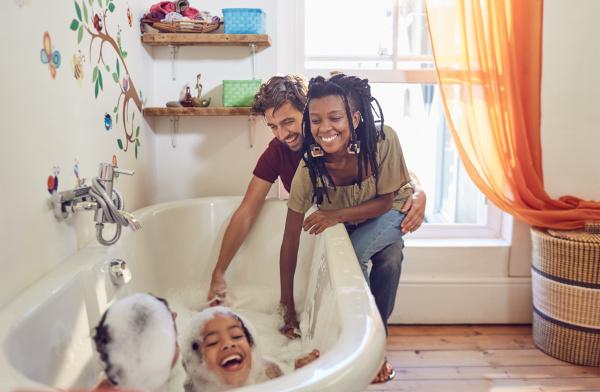 parents giving playful daughters bubble bath