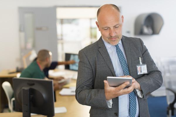 male administrator using digital tablet in