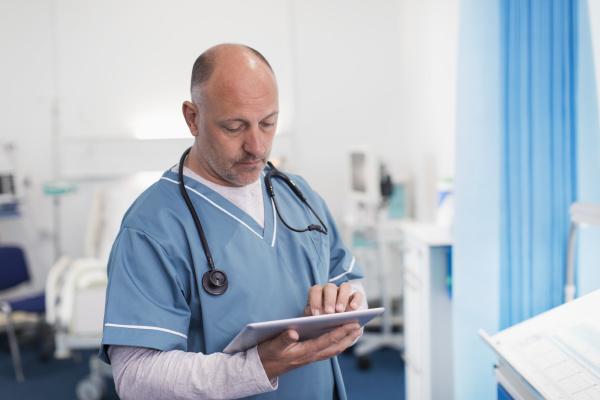 male doctor using digital tablet in