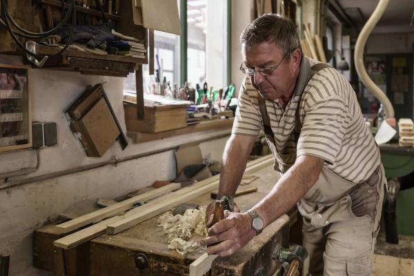 craftsman in carpentry workshop smoothing wooden