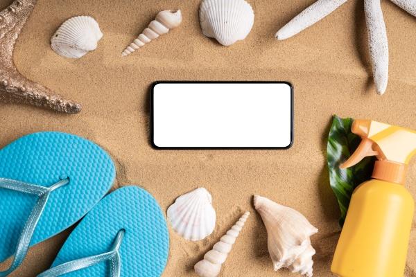 mobile phone and shells on sand