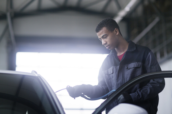 workman fixing car windshield in workshop