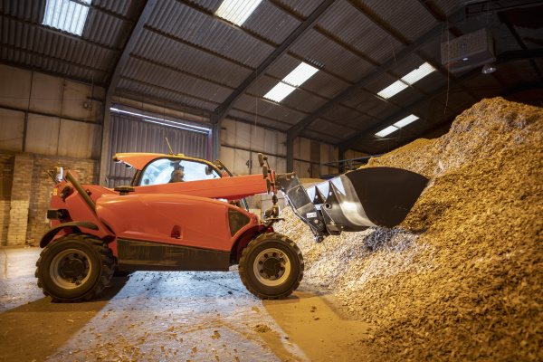 digger with pile of wood chips
