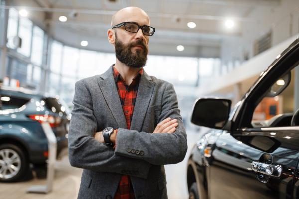 bearded man poses at pickup truck