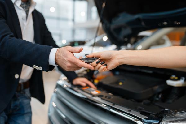 man and salesgirl choosing auto in