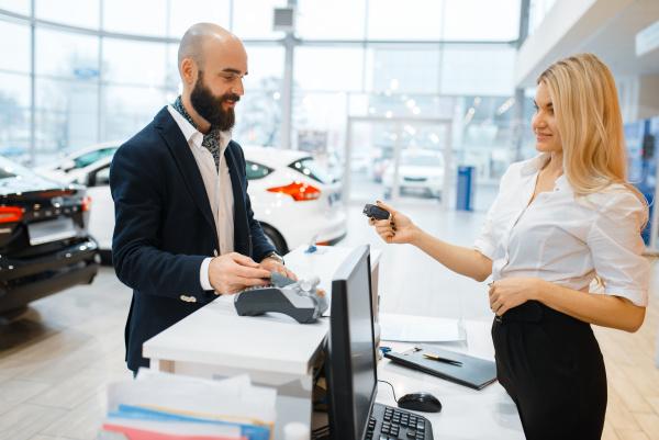 female seller gives keys to man