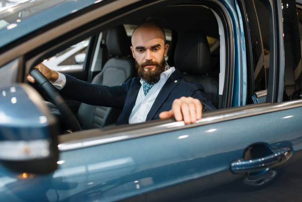smiling man poses in automobile
