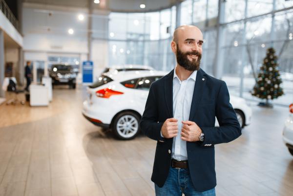 smiling man poses in car dealership