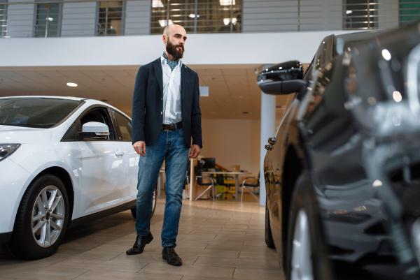 businessman choosing transport in car dealership