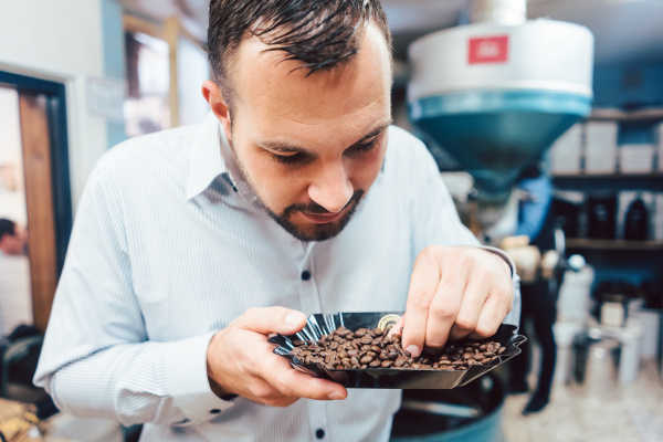 man with freshly roasted coffee beans