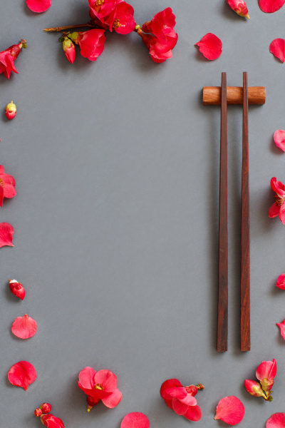 chopsticks and pink flowers on gray