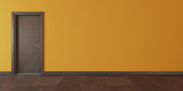 brown wooden door with yellow wall