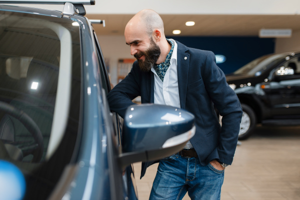 smiling man poses at automobile in