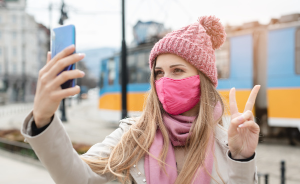 woman doing victory sign making selfie