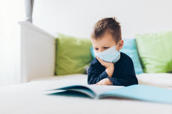 unhappy child wearing respiratory mask as