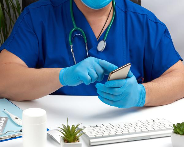 doctor in blue medical uniform sits