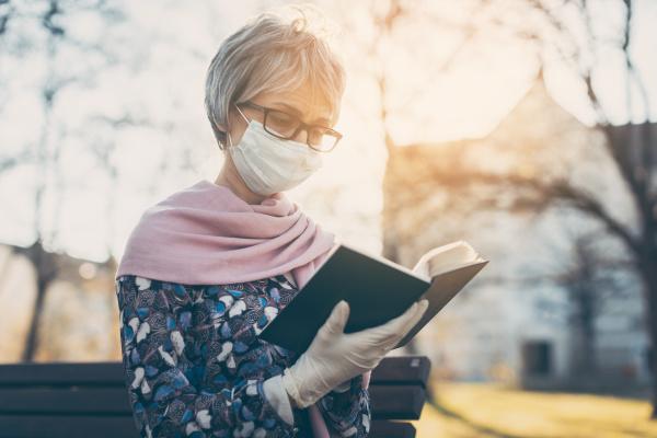 senior lady with face mask reading