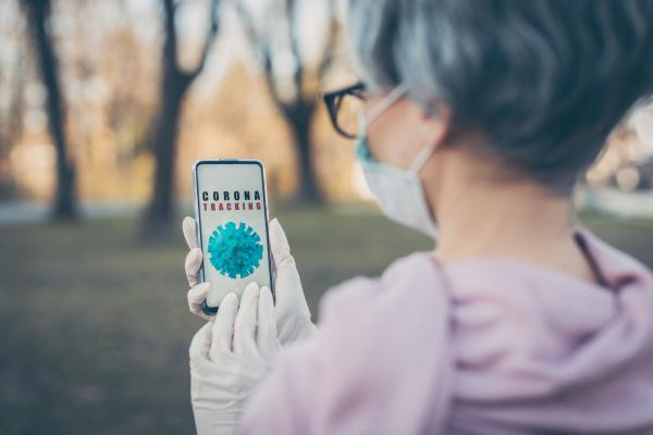 senior woman using coronavirus tracking app
