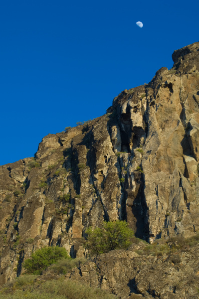 moon over a cliff in the