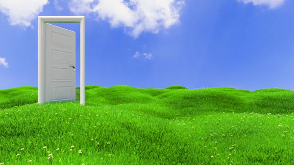 open door on green flowery hills