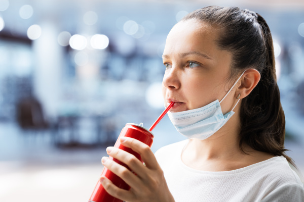 woman drinking soda in face mask