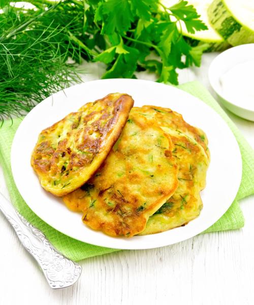 pancakes of zucchini on light wooden