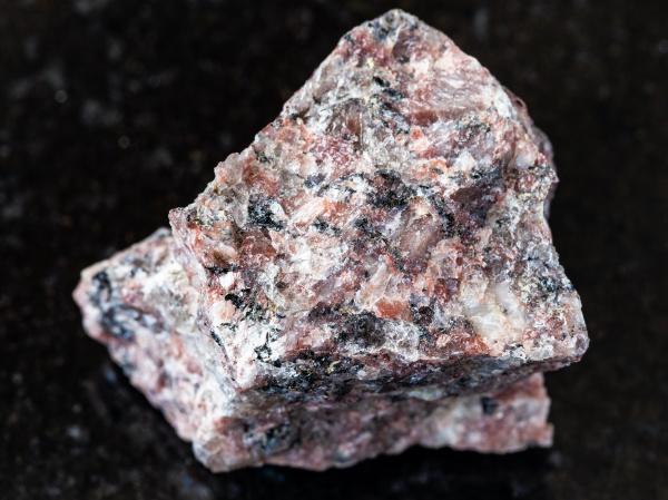 unpolished pink granite rock on black