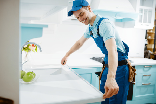 male furniture maker in uniform measures