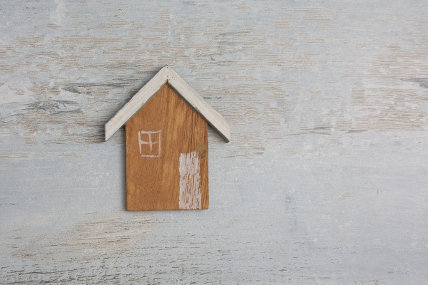 tiny wooden house on distressed background