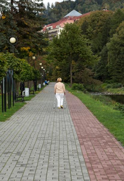 senior woman doing nordic walking in