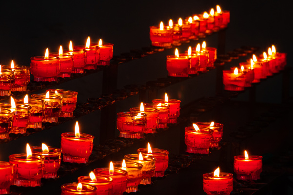 small burning church candles in red