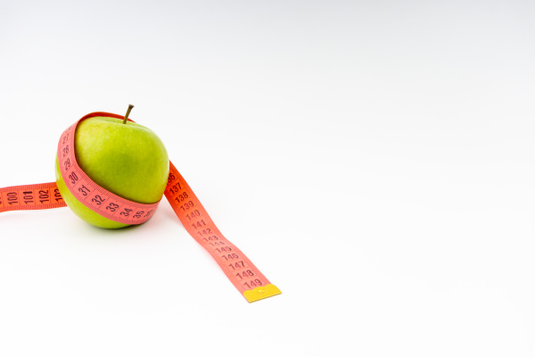 green apple with red measuring tape