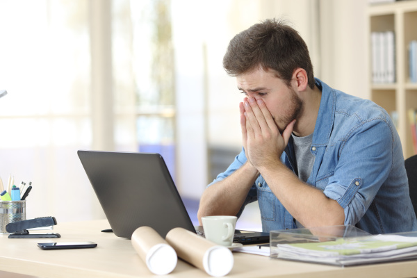 worried entrepreneur looking at laptop at