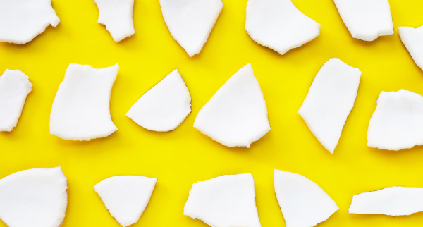 coconut cut pieces on yellow background