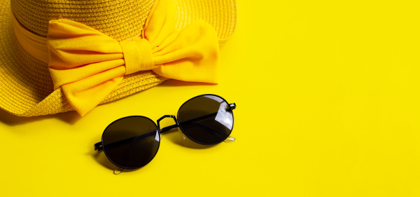 sunglasses with summer hat on yellow