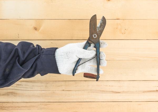 hand in glove holding plier
