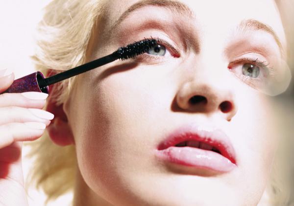 close up young woman applying mascara