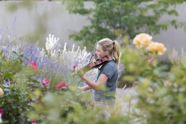 teenage girl standing among flowering roses