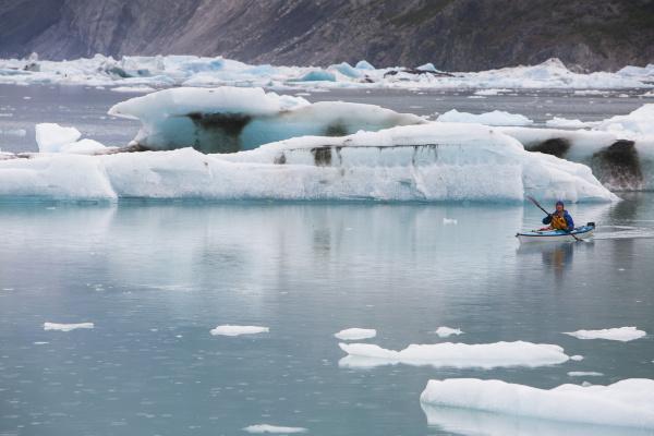 sea kayakers paddling in glacial lagoon