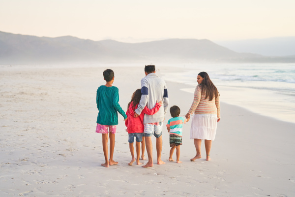 affectionate family walking on ocean beach