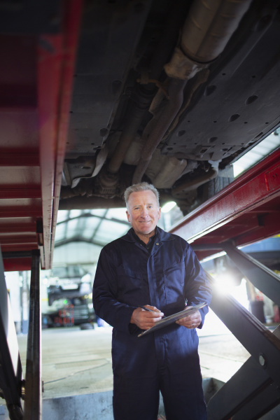 portrait confident male mechanic with clipboard