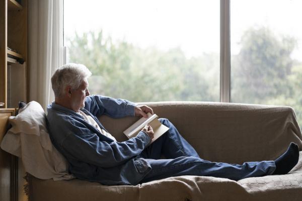 senior man reading book while relaxing