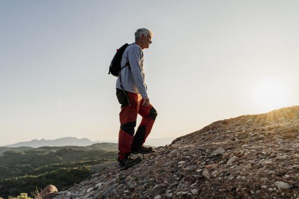 active senior man hiking up on